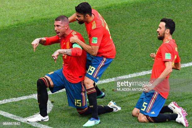 TOPSHOT Spain's defender Sergio Ramos celebrates with Spain's forward Diego Costa and Spain's midfielder Sergio Busquets after Russia scored an own...