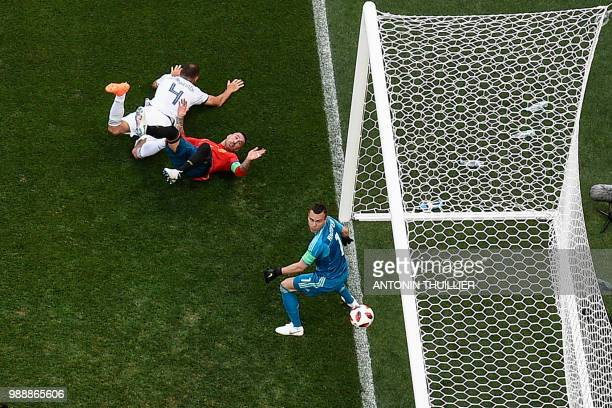 TOPSHOT Spain's defender Sergio Ramos falls as Russia's defender Sergey Ignashevich scores an own goal during the Russia 2018 World Cup round of 16...