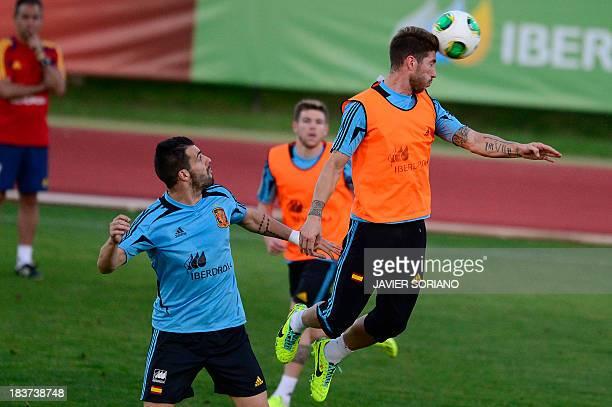 Spain's defender Sergio Ramos heads the ball past Spain's forward Alvaro Negredo during a training session at Las Rozas Sport City near Madrid on...