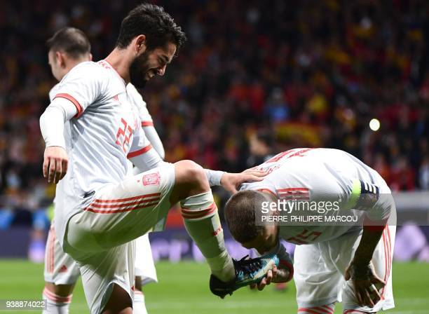 Spain's defender Sergio Ramos kisses the foot of Spain's midfielder Isco after he scored a goal during a friendly football match between Spain and...