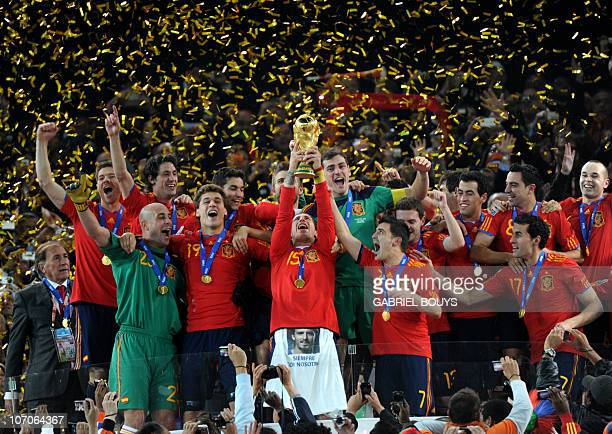 Spain's defender Sergio Ramos raises the trophy as Spain's national football team players celebrate winning the 2010 World Cup football final...