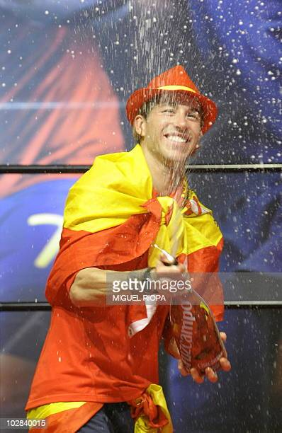 Spain's defender Sergio Ramos sprays champagne on a stage set up for the Spanish team victory ceremony in Madrid on July 12 2010 a day after they won...