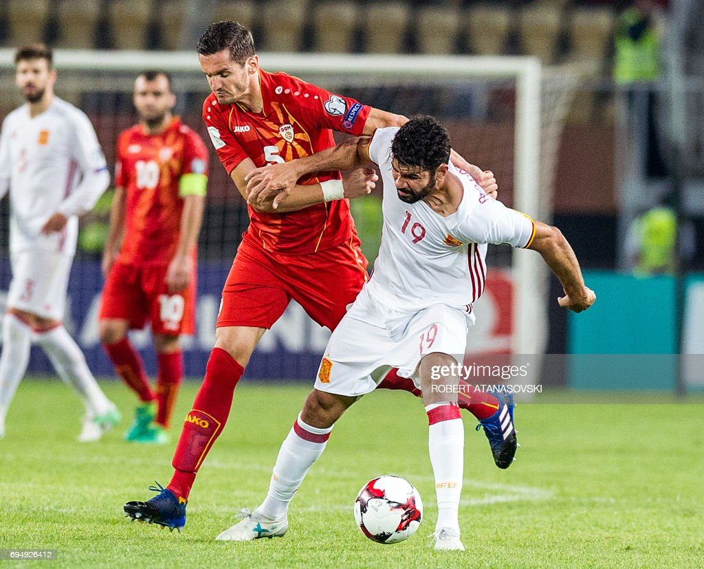 Spain's Diego Kosta (R) vies with Macedonia's Daniel Mojsov during the FIFA World Cup 2018 qualification football match between Italy and Liechtenstein at the Dacia Arena Stadium in Udine, on June 11, 2017. / AFP PHOTO / Robert ATANASOVSKI