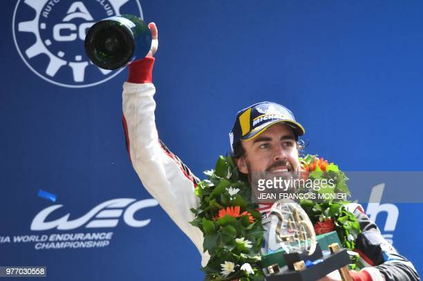 Spain's driver Fernando Alonso celebrates on the podium with his trophy after winning the 86th Le Mans 24hours endurance race at the Circuit de la...
