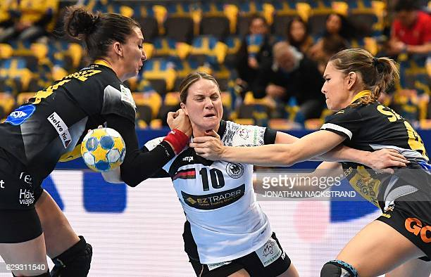 Spain's Elizabet Chavez and Judith Sans try to stop Germany's Anna Loerper as she prepares to throw the ball during the Women's European Handball...