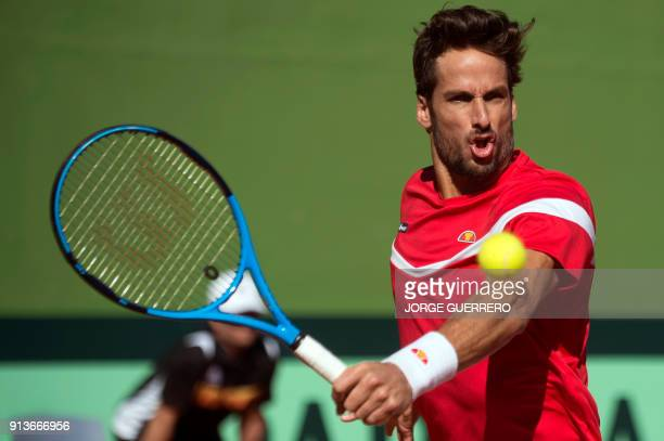 Spain's Feliciano Lopez returns the ball during his tennis doubles match against Britons Jamie Murray and Dominic Inglot of the first round of the...