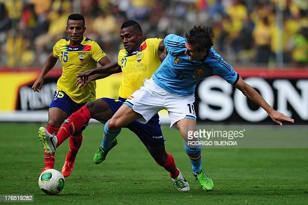 Spain's Fernando Llorente vies for the ball with Ecuador's Gabriel Achilier and Pedro Quinonez during a friendly football match at Monumental stadium...