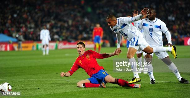 Spain's Fernando Torres goes down in the penalty area under a tackle by Honduras's Sergio Mendoza