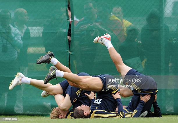 Spain's Fernando Torres Sergio Ramos and Joan Capdevila stretch during a training session on June 15 2008 at Sportplatz Kampl in Neustift near...