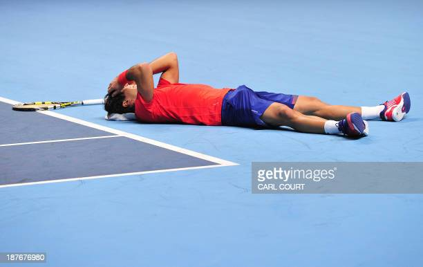 Spain's Fernando Verdasco lies on the court as he celebrates beating with his partner Spain's David Marrero US player Bob Bryan and US player Mike...