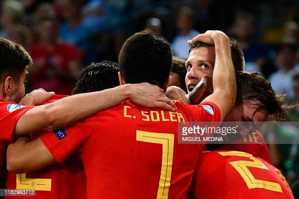 Spain's forward Dani Olmo celebrates with Spain's midfielder Fabian Ruiz and teammates after scoring his team's second goal during the final match of...
