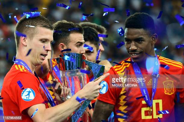 Spain's forward Dani Olmo holds the winners' trophy next to Spain's defender Junior Firpo after Spain won the final match of the UEFA U21 European...