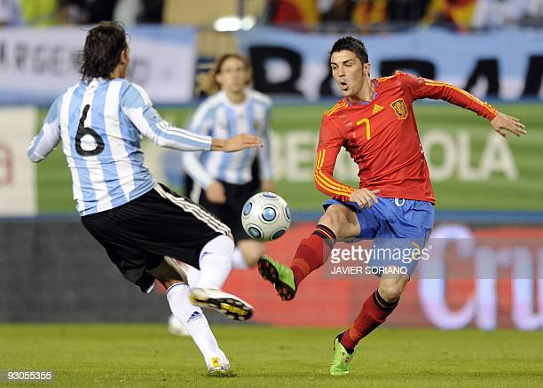 Spain's forward David Villa vies for the ball with Argentina's Gabriel Heinze during a friendly football match at the Vicente Calderon stadium in...
