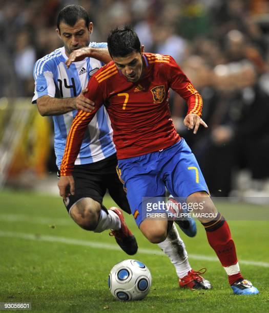 Spain's forward David Villa vies with Argentina's Javier Mascherano during their FIFA World Cup 2010 friendly football match at Vicente Calderon...