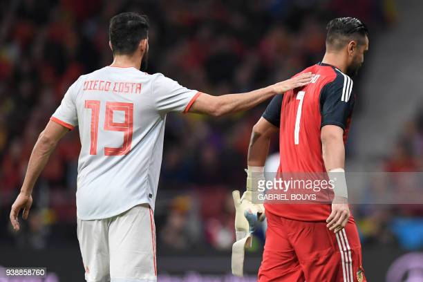 Spain's forward Diego Costa consoles Argentina's goalkeeper Sergio Romero as he walks off the pitch after getting injured during a friendly football...
