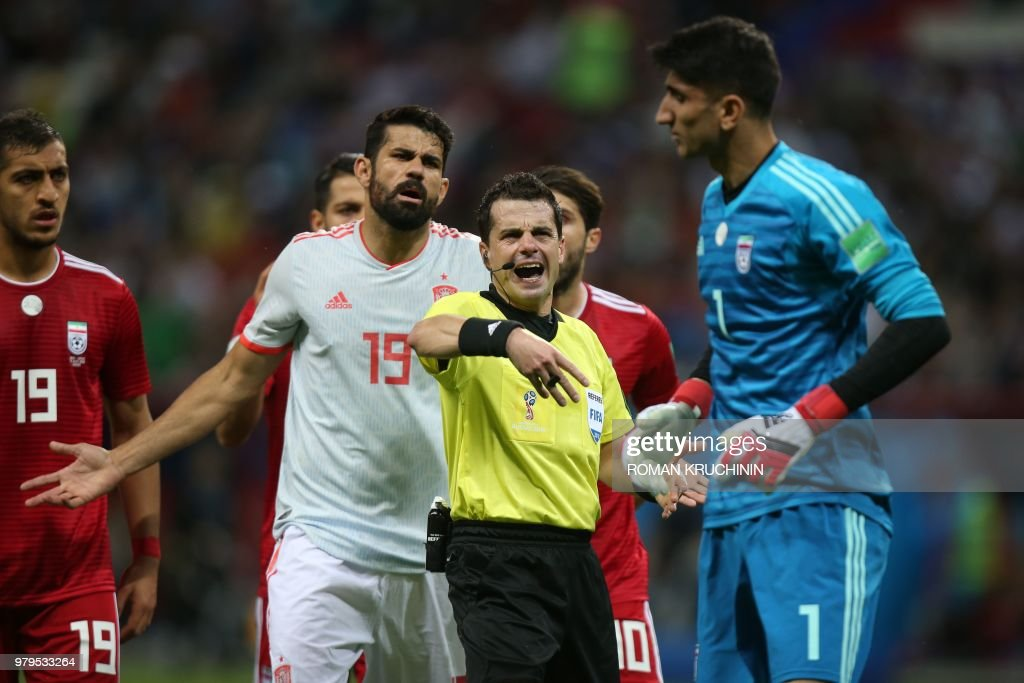 Spain's forward Diego Costa (#19) gestures as Uruguayan referee Andres Cunha speaks to Iran's goalkeeper Alireza Beiranvand during the Russia 2018 World Cup Group B football match between Iran and Spain at the Kazan Arena in Kazan on June 20, 2018. (Photo by Roman Kruchinin / AFP) / RESTRICTED