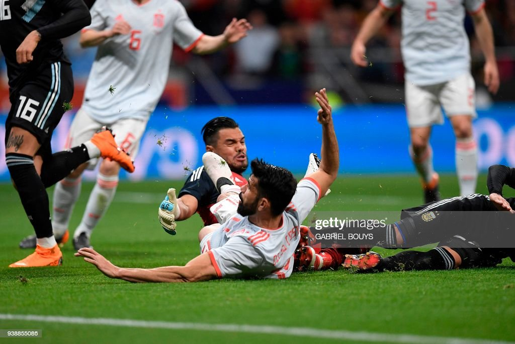 Spain's forward Diego Costa (L) reacts as he falls after scoring a goal during a friendly football match between Spain and Argentina at the Wanda Metropolitano Stadium in Madrid on March 27, 2018. /