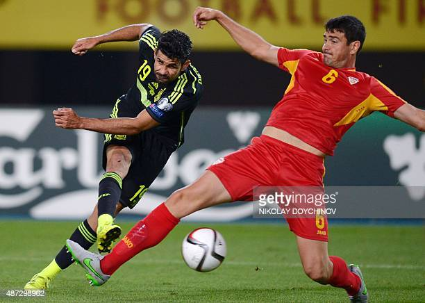 Spain's Forward Diego Costa shoots the ball past Macedonia's Defender Vanche Shikov during the Euro 2016 Group C qualifying football match between...