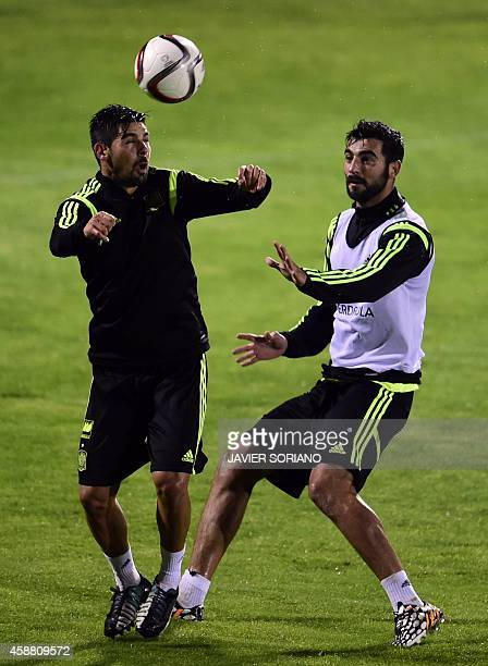 Spain's forward Manuel Agudo and Spain's defender Raul Albiol take part in a training session on November 11 2014 at the Sport City training ground...