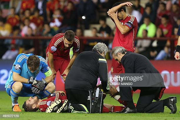 Spain's forward Paco Alcacer is attended to by medical staff during the Euro 2016 qualifying football match Spain vs Luxembourg at Las Gaunas stadium...