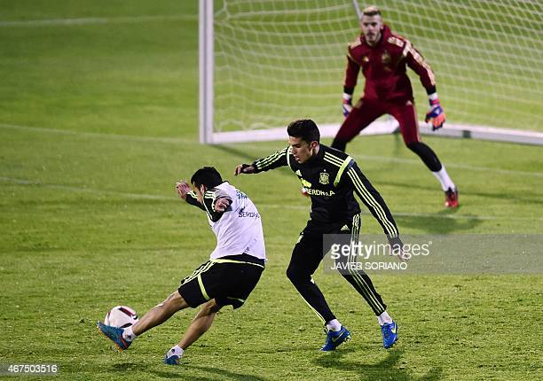 Spain's forward Pedro Rodriguez kicks the ball beside Spain's defender Marc Bartra during a training session at the Sport City training ground in Las...