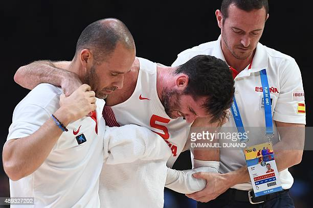 Spain's forward Rudy Fernandez is escorted out of the court after sustaining an injury during the final basketball match between Spain and Lithuania...