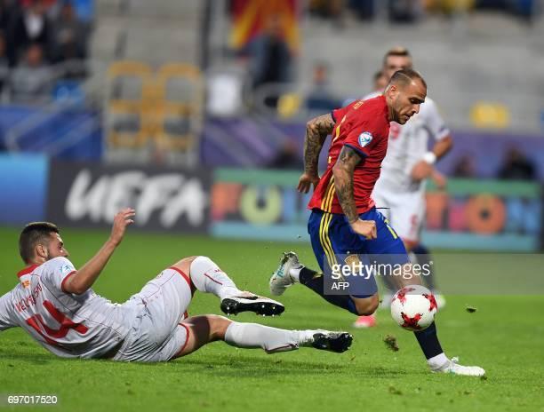 Spain's forward Sandro Ramirez is tackled by Macedonia's defender Darko Velkoski during the UEFA U21 European Championship Group B football match...