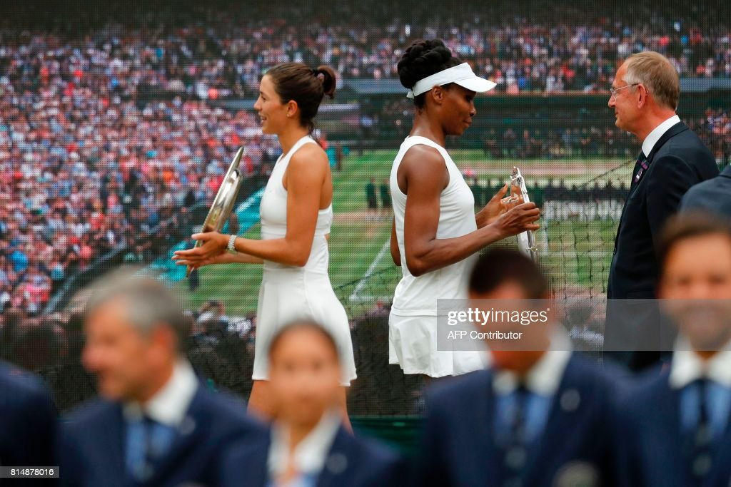 Spain's Garbine Muguruza (L) and US player Venus Williams pose with their trophies after Muguruza won the women's singles final on the twelfth day of the 2017 Wimbledon Championships at The All England Lawn Tennis Club in Wimbledon, southwest London, on July 15, 2017. Muguruza won 7-5, 6-0. / AFP PHOTO / Adrian DENNIS / RESTRICTED