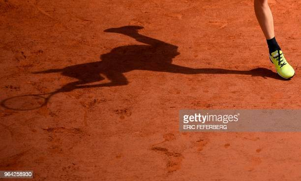 TOPSHOT Spain's Garbine Muguruza casts a shadow on court as she plays a forehand return to France's Fiona Ferro during their women's singles second...