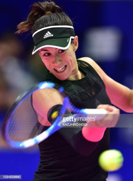 Spain's Garbine Muguruza hits a return against Switzerland's Belinda Bencic during their women's singles first round match at the Pan Pacific Open...