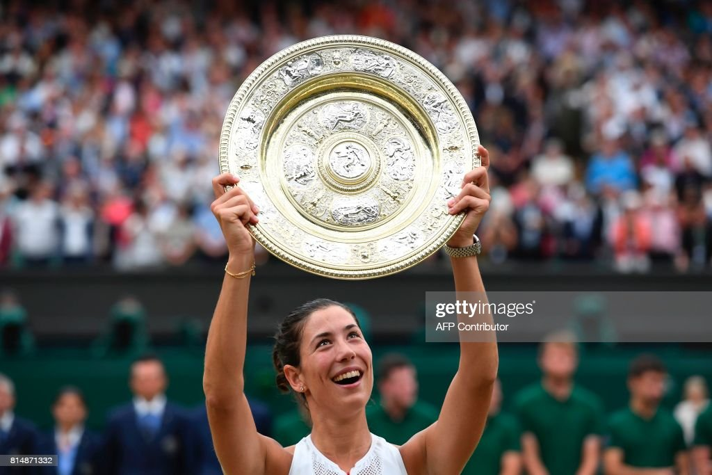 Spain's Garbine Muguruza holds up The Venus Rosewater Dish as she celebrates beating US player Venus Williams to win the women's singles final on the twelfth day of the 2017 Wimbledon Championships at The All England Lawn Tennis Club in Wimbledon, southwest London, on July 15, 2017. Muguruza won 7-5, 6-0. / AFP PHOTO / Glyn KIRK / RESTRICTED