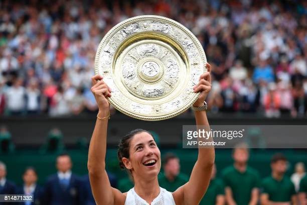 Spain's Garbine Muguruza holds up The Venus Rosewater Dish as she celebrates beating US player Venus Williams to win the women's singles final on the...