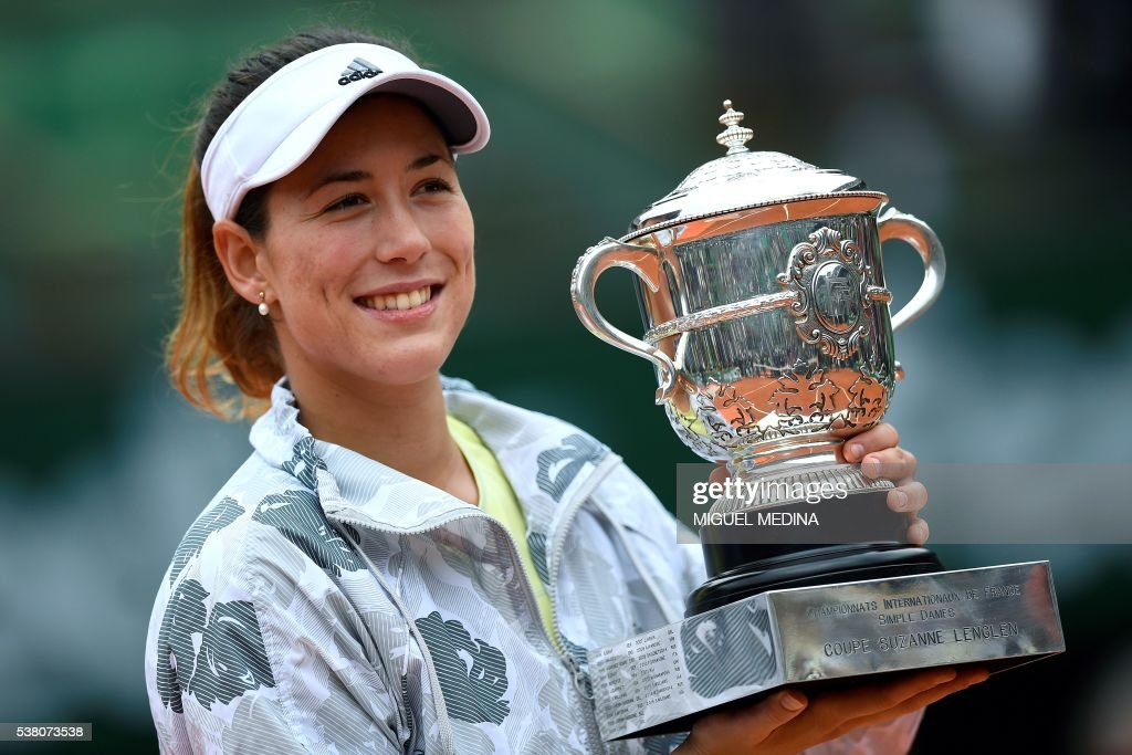 TOPSHOT - Spain's Garbine Muguruza poses with the trophy after winning the women's final match against US player Serena Williams at the Roland Garros 2016 French Tennis Open in Paris on June 4, 2016. /