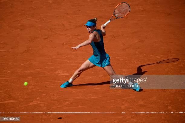 TOPSHOT Spain's Garbine Muguruza returns the ball to Romania's Simona Halep during their women's singles semifinal match on day twelve of The Roland...