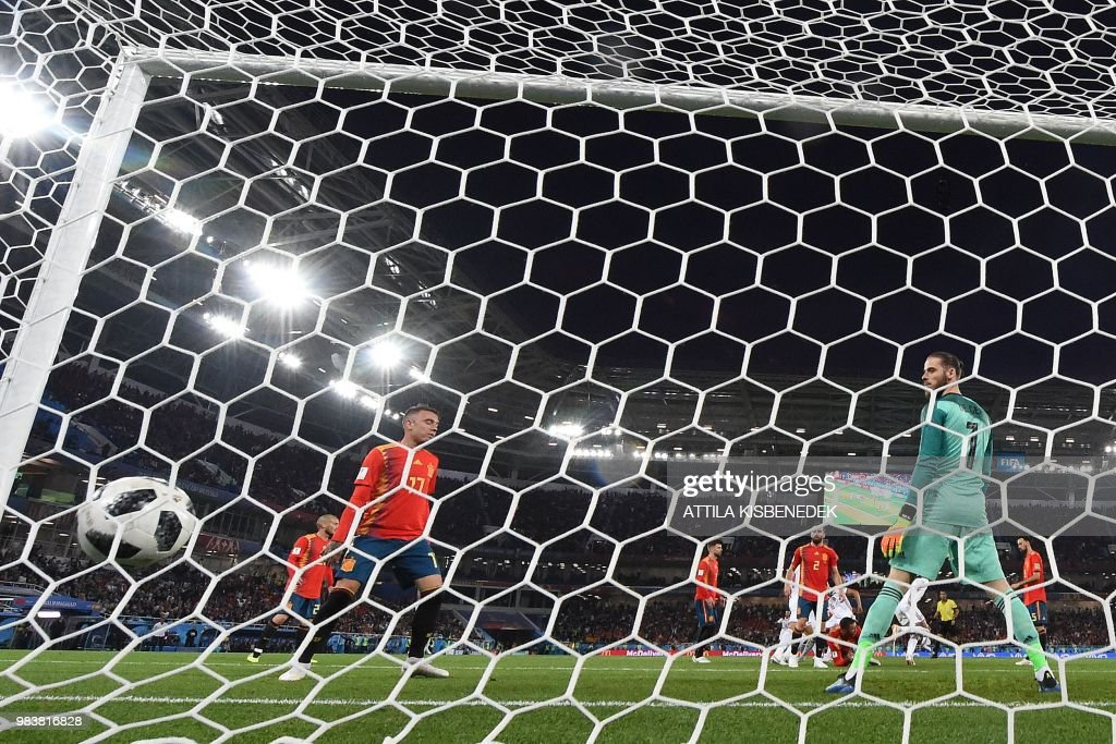 TOPSHOT - Spain's goalkeeper David De Gea (R) eyes the ball as he concedes a goal during the Russia 2018 World Cup Group B football match between Spain and Morocco at the Kaliningrad Stadium in Kaliningrad on June 25, 2018. (Photo by Attila KISBENEDEK / AFP) / RESTRICTED