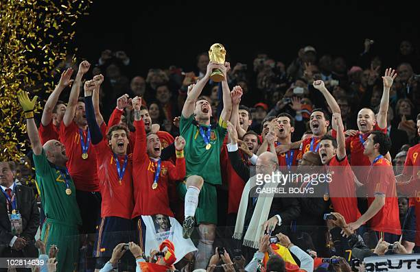 Spain's goalkeeper Iker Casillas raises the trophy as Spain's national football team players celebrate with FIFA President Sepp Blatter and South...