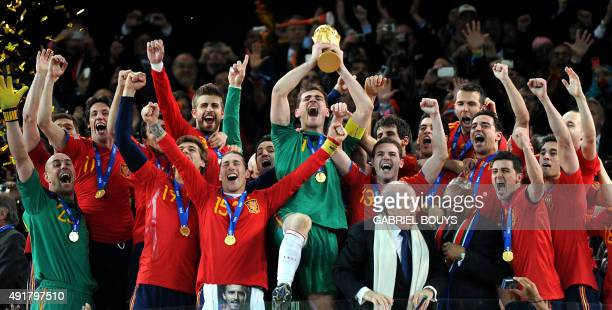 Spain's goalkeeper Iker Casillas raises the trophy handed to him by FIFA President Sepp Blatter and South Africas President Jacob Zuma as Spain's...