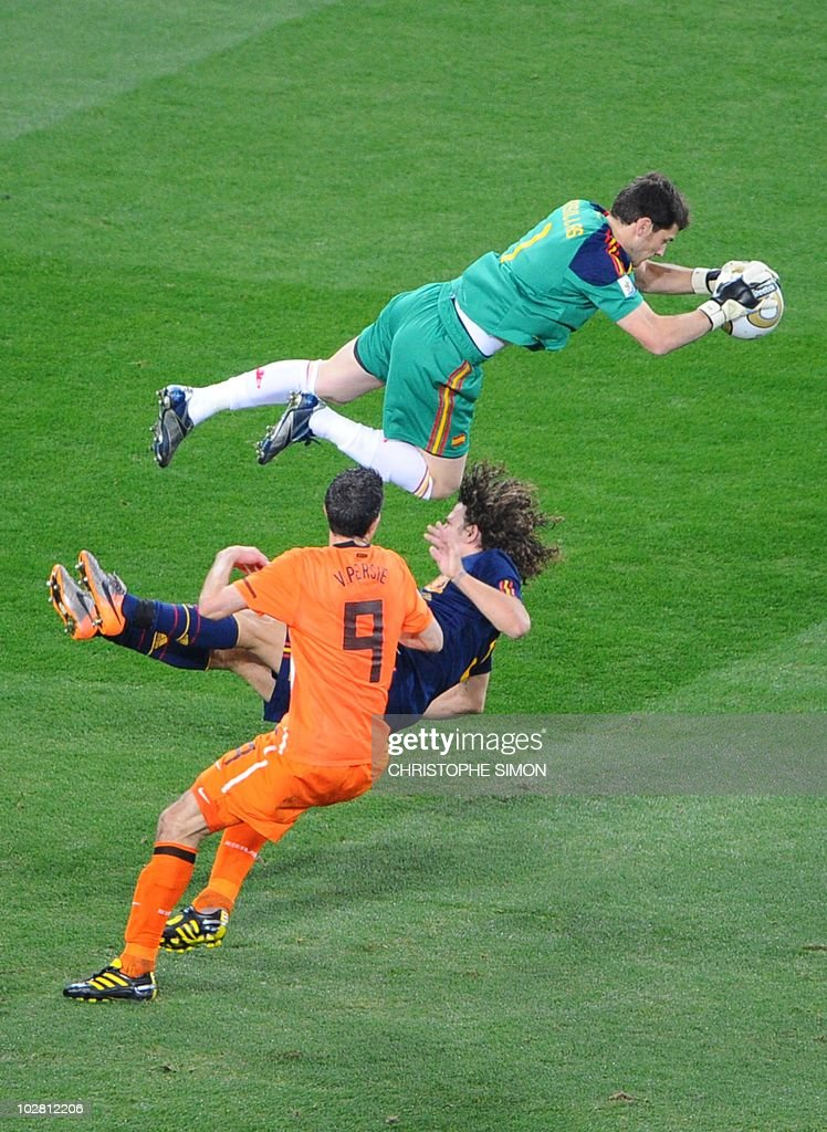 Spain's goalkeeper Iker Casillas saves a ball jumping over Spain's defender Carles Puyol flanked by Netherlands' striker Robin van Persie during the 2010 World Cup football final between the Netherlands and Spain on July 11, 2010 at Soccer City stadium in Soweto, suburban Johannesburg. NO