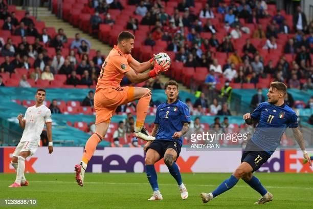 Spain's goalkeeper Unai Simon gathers the ball ahead of Italy's forward Ciro Immobile during the UEFA EURO 2020 semi-final football match between...