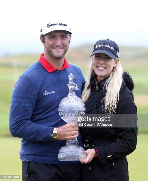 Spain's Jon Rahm celebrates winning the Dubai Duty Free Irish Open with girlfriend Kelley Cahill and the trophy at Portstewart Golf Club
