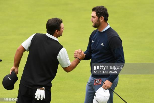 Spain's Jon Rahm shakes hands with US golfer Patrick Reed on the 18th green during the third round of the British Open golf Championships at Royal...