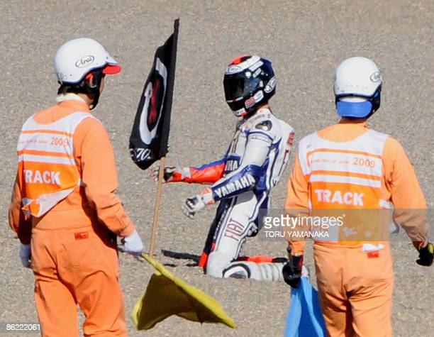 """Spain's Jorge Lorenzo plants a flag showing his symbol """"Lorenzo Land"""" to illustrate """"the conquests of Lorenzo"""" on a sand trap during his victory run..."""