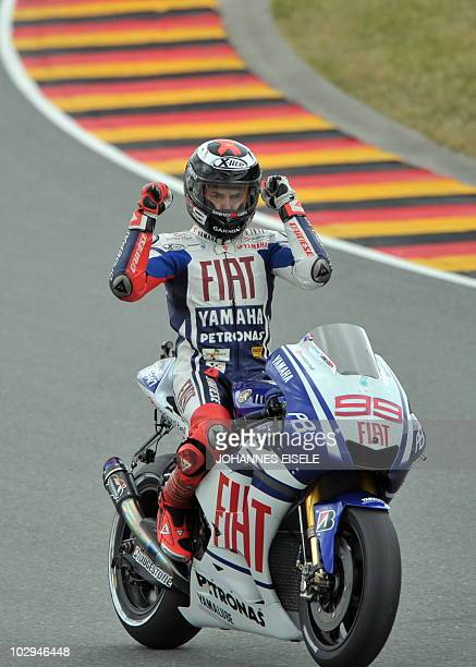 Spain's Jorge Lorezno of the Fiat Yamaha team celebrates on his bike after the qualifying practice of the MotoGP race at the Sachsenring Circuit on...