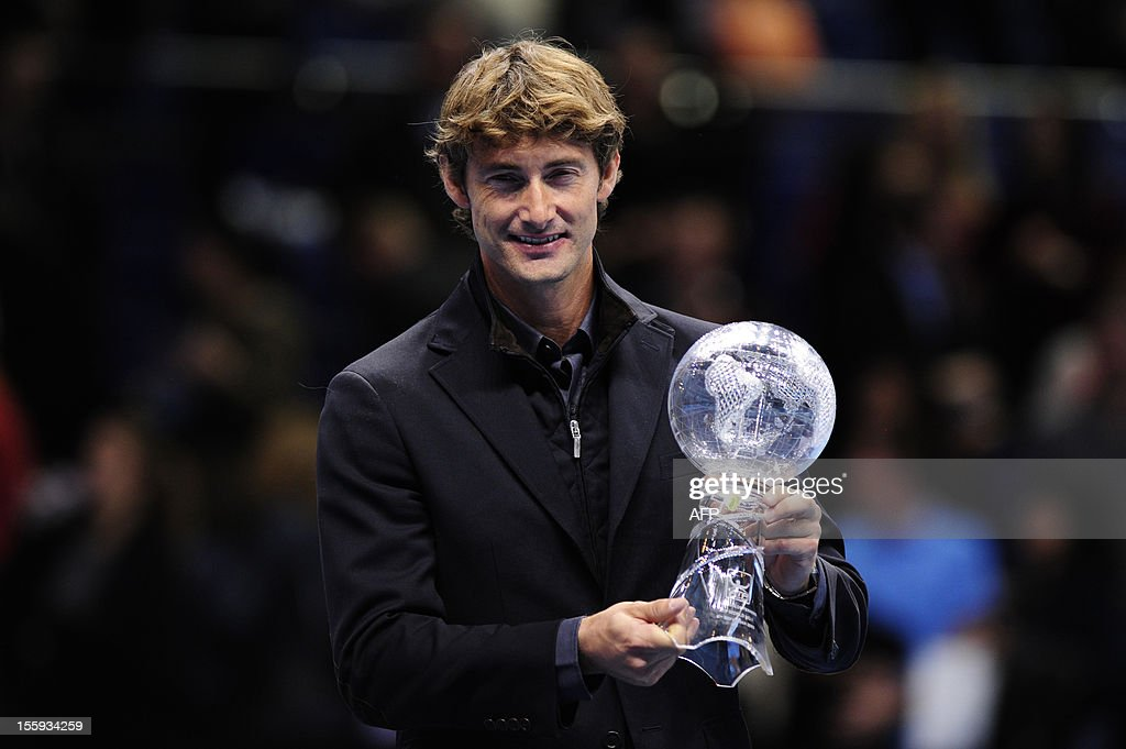 Spain's Juan Carlos Ferrero holds a trophy presented to him to mark his retirement after 13 years on the ATP tour on the fifth day of the ATP World Tour Finals tennis tournament in London on November 9, 2012. Former world number one Juan Carlos Ferrero retired from professional tennis in October 2012 after a career in which he won 16 ATP tour singles titles including a grand slam.