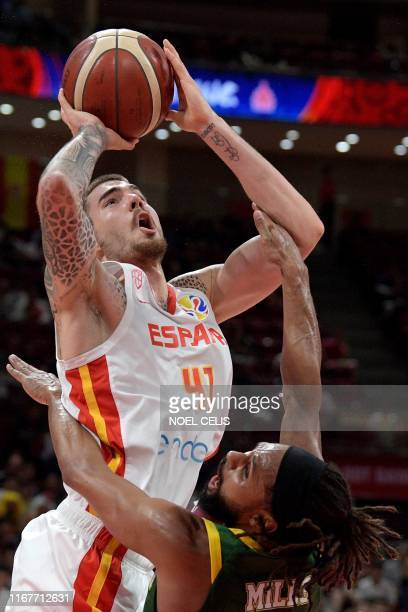 Spain's Juan Hernangomez takes a shot as Australia's Patty Mills tries to block during the Basketball World Cup semifinal game between Australia and...