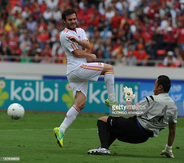 Spain's Juan Mata tries to shoot over Costa Rican goalie Keilor Navas during a friendly match at the National Stadium in San Jose on November 15 2011...
