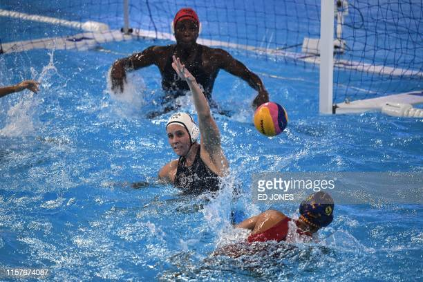 Spain's Judith Forca Ariza throws the ball as USA's Alys Williams and USA's goalkeeper Ashleigh Johnson attempt to block it during the women's final...
