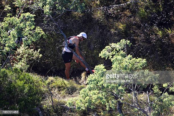 Spain's Kilian Jornet treats an injury at his knee as he competes in the Mafate circus during the 21st Diagonale des Fous or Grand Raid a 164 km raid...
