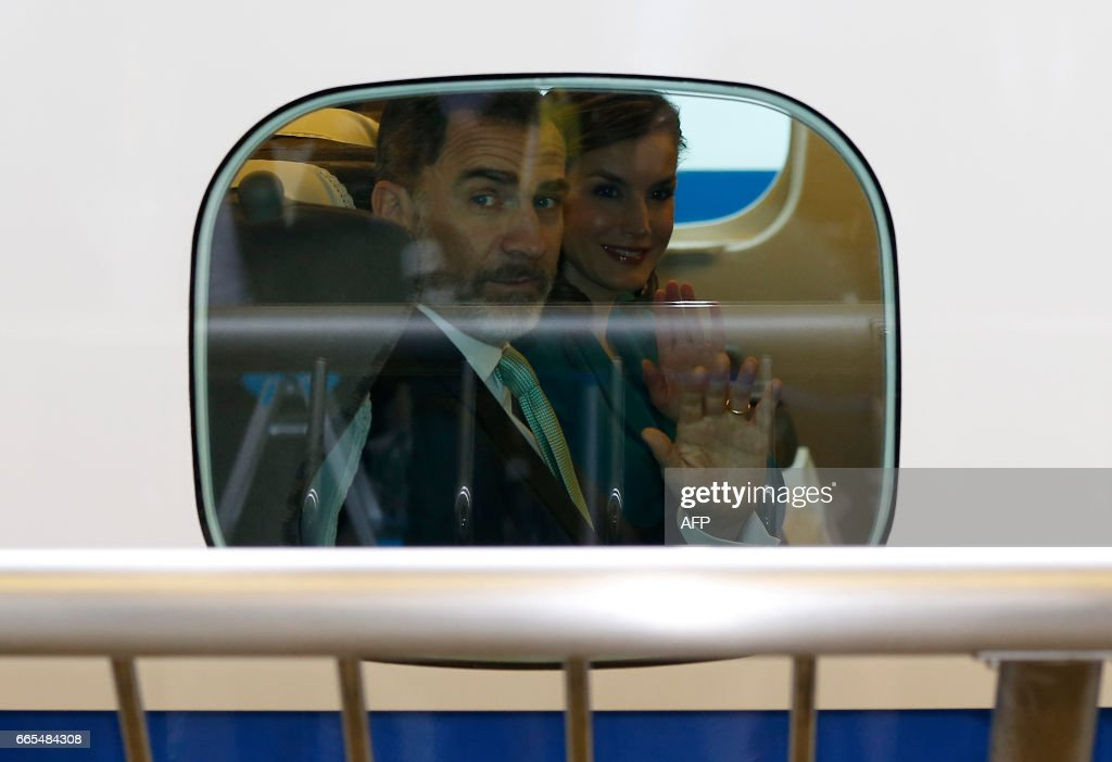 Spain's King Felipe (L) and Queen Letizia wave to well-wishers from a window of a Shinkansen bullet train as they leave on their one-day trip to Shizuoka with Japan's Emperor Akihito and Empress Michiko, at Tokyo station in Tokyo on April 7, 2017. The Spanish royal couple is on a four-day state visit to Japan. /
