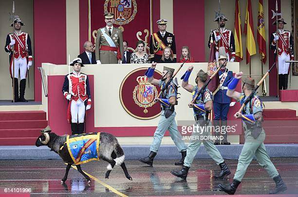 TOPSHOT Spain's King Felipe IV Spain's Queen Letizia Spain's princess Sofia and princess Leonor watch troops and a mascot march during the Spanish...